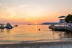 Härlig stillsam solnedgång över stranden och vatten med uppblåsbara glidbanor och torn mot horisonten arkivfoto