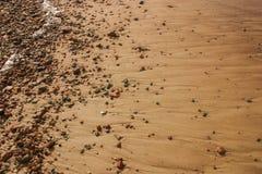 Härlig strand med färgrika kiselstenar i sand Arkivbilder