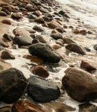 Härlig strand med färgrika kiselstenar i sand Arkivfoton