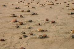 Härlig strand med färgrika kiselstenar i sand Arkivbild