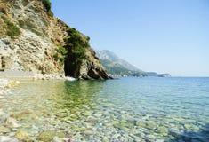 Härlig strand med rent vatten och stenar royaltyfria foton