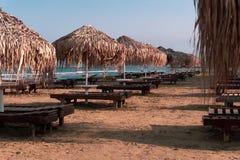 Härlig strand med soldagdrivare på solnedgången arkivfoton