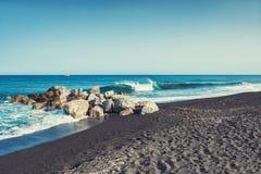 Härlig strand med turkosvatten och svart sand arkivbilder