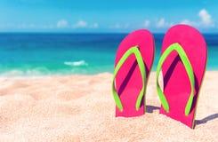 härlig strand Sätta på land sandaler på den sandiga kustsommarholidaen Royaltyfria Bilder