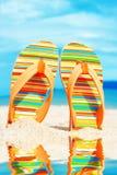härlig strand Sätta på land sandaler på den sandiga kustsommarholidaen Arkivfoton