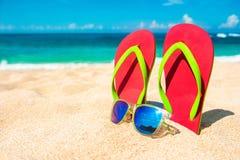 härlig strand Sätta på land sandaler på den sandiga kustsommarholidaen Royaltyfri Fotografi