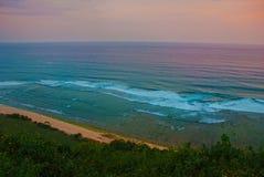 Härlig strand, sikt av havet under solnedgång Uluwatu bali indonesia Arkivfoton