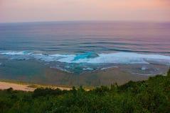 Härlig strand, sikt av havet under solnedgång Uluwatu bali indonesia Arkivfoto