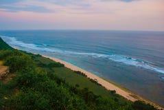 Härlig strand, sikt av havet under solnedgång Uluwatu bali indonesia Royaltyfri Bild