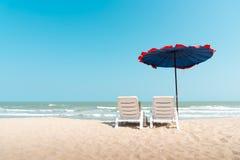 härlig strand Stolar och paraply på den sandiga tropiska stranden Royaltyfria Foton