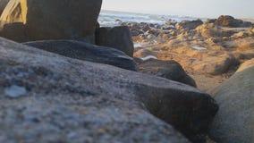 Härlig stranddag med vattnet, klipporna och sanden Royaltyfri Foto