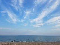 Härlig strandsikt för eftermiddag med moln och blå himmel Arkivfoto