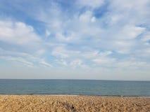 Härlig strandsikt för eftermiddag med moln och blå himmel Royaltyfria Bilder