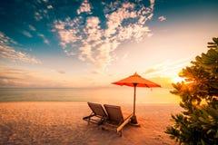 Härlig strandsolnedgång med solsängar och avslappnande lynne royaltyfri fotografi