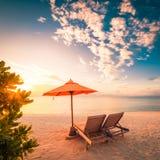 Härlig strandsolnedgång med solsängar och avslappnande lynne royaltyfria foton