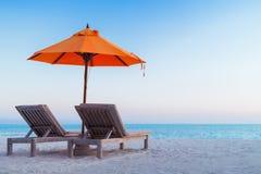 Härlig strandsolnedgång med solsängar och avslappnande lynne arkivbilder