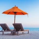 Härlig strandsolnedgång med solsängar och avslappnande lynne royaltyfri foto