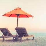 Härlig strandsolnedgång med solsängar och avslappnande lynne royaltyfria bilder