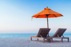 Härlig strandsolnedgång med solsängar och avslappnande lynne arkivbild