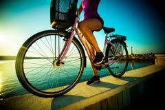 Härlig streightkvinna med cykeln på solnedgång royaltyfria foton