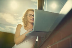 Härlig student som arbetar med bärbara datorn bredvid tegelsten-väggen Arkivbild