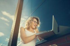 Härlig student som arbetar med bärbara datorn bredvid tegelsten-väggen Arkivbilder