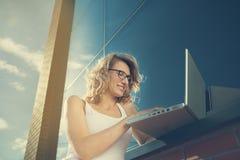 Härlig student som arbetar med bärbara datorn bredvid tegelsten-väggen Royaltyfri Bild