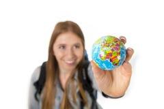 Härlig studentflicka som rymmer det lilla världsjordklotet i hennes hand som väljer feriedestinationen i loppturismbegrepp Royaltyfri Foto