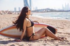 Härlig surfarebrunettflicka med brädet som kopplar av på stranden av Dubai Arkivfoto