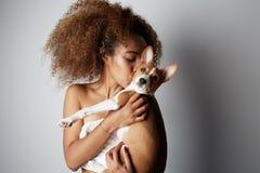 Härlig svart amerikansk afrikansk flicka som omfamnar valpen på vit bakgrund Studiostående av den vita lockande kvinnlign royaltyfria foton