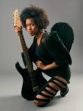 Härlig svart flicka med ängelvingar och den elektriska gitarren arkivfoto