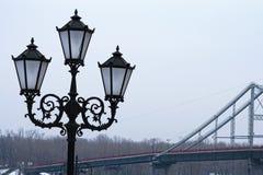 Härlig svart gatalykta för tre lampor, slut upp fotoet Fot- bro i bakgrunden Vintermorgonsikt Royaltyfria Bilder