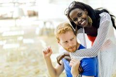 Härlig svart kvinna som kramar den ljust rödbrun pojkvännen royaltyfri foto