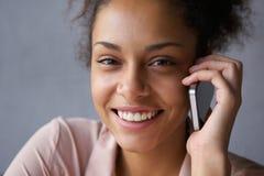 Härlig svart kvinna som ler med mobiltelefonen Fotografering för Bildbyråer