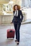 Härlig svart kvinna som ler och bär en rullande resväska i stads- bakgrund fotografering för bildbyråer