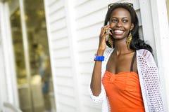 Härlig svart kvinna som talar på telefonen och att le royaltyfri foto