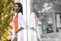 Härlig svart kvinna som talar på telefonen och att le royaltyfria foton