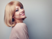 Härlig tand som ler kvinnan med kort blont hår som ser happ Arkivfoto