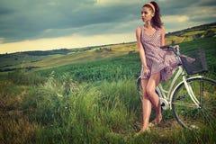 Härlig tappningflicka som sitter bredvid cykeln, sommartid royaltyfri fotografi