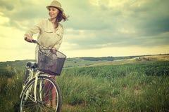 Härlig tappningflicka som sitter bredvid cykeln, sommartid royaltyfria foton