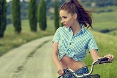 Härlig tappningflicka som sitter bredvid cykeln, sommartid arkivfoto