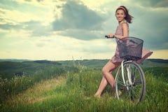 Härlig tappningflicka som sitter bredvid cykeln, sommartid arkivfoton