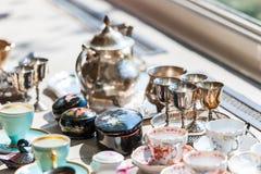 Härlig tappninguppsättning av koppar och tefat i porslin och silver royaltyfri bild