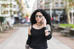 Härlig tatuerad kvinna med solglasögon som talar vid telefonen Fotografering för Bildbyråer