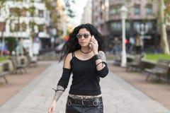 Härlig tatuerad kvinna med solglasögon som talar vid telefonen Royaltyfri Fotografi