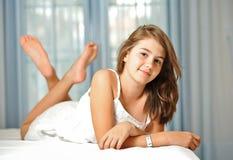 Härlig teen flicka hemma i den vita klänningen Arkivbilder