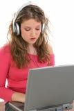 härlig teen flickahörlurarbärbar dator Fotografering för Bildbyråer