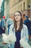 härlig teen flickastående Vita duvor sitter på deras händer royaltyfri foto
