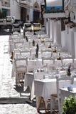 Härlig terrass av en restaurang i en medelhavs- by i solljuset - som dekoreras all i vit Arkivbild
