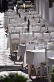 Härlig terrass av en restaurang i en medelhavs- by i solljuset - som dekoreras all i vit Royaltyfri Foto